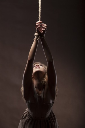 Beautiful young woman with a rope around the hands on dark brown background, studio shot.