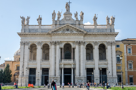 Roma, Italy - October 2015: Foreign tourists strolling and being photographed on an excursion near the main entrance Basilica di San Giovanni in Laterano