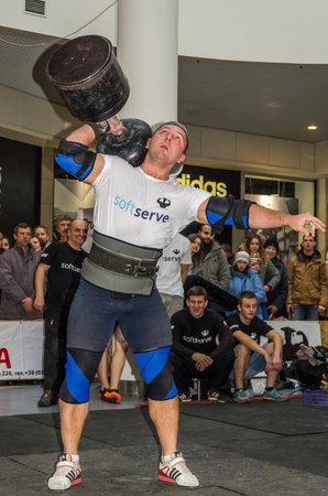 LVIV, UKRAINE - NOVEMBER 2016: Strong athlete bodybuilder strongman lifts heavy dumbbell in front of audience