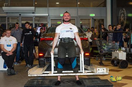 LVIV, UKRAINE - NOVEMBER 2016: Strong athlete strongman lifts a heavy car Toyota Corolla