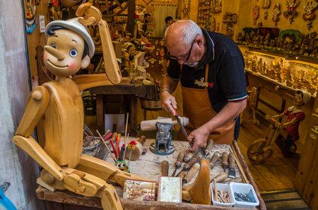 Foto de ROMA, ITALY - JULY 2017: Workshop where the master scrutinizes the handmade traditional wooden toys of Pinocchio - Imagen libre de derechos