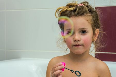 Foto de Little adorable baby girl blow bubbles while bathing in the bathroom - Imagen libre de derechos