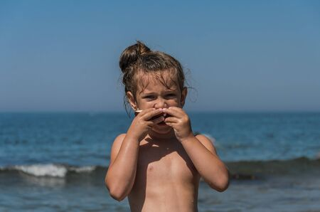 Photo pour Little charming girl child eating coconut on the sea beach - image libre de droit