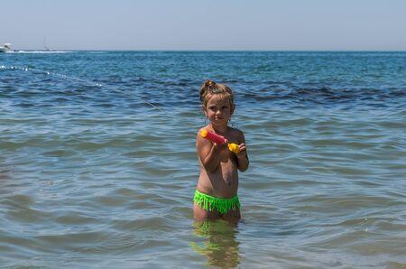 Foto de Little charming girl child plays in the sea and sprays a water gun - Imagen libre de derechos