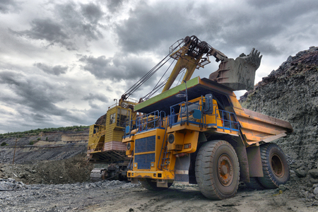 Photo pour Large quarry dump truck. Loading the rock in the dumper. Loading coal into body work truck. Mining truck mining machinery, to transport coal from open-pit - image libre de droit