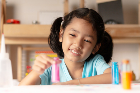 The little girl is testing color in glass and looking with smile and happiness. Select focus shallow depth of fied.
