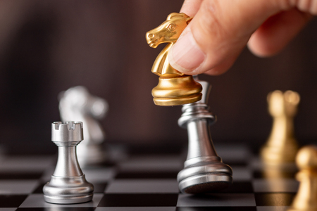 Foto de hand holding gold horse attack silver king in game on the chessboard with wooden background - Imagen libre de derechos