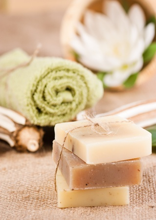 Spa setting with natural soaps and lotus flower. Focus is on the bow.
