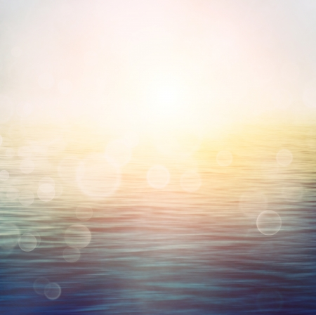 Abstract nature summer or spring ocean sea background  Small waves on water surface in motion blur with bokeh lights from sunrise
