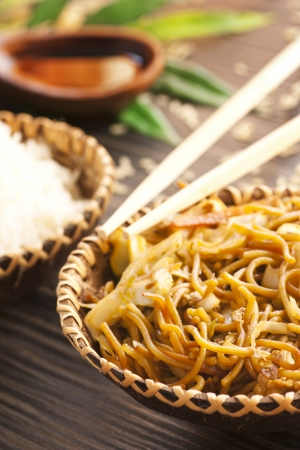Chinese food. Egg noodles with chicken and vegetables, steamed rice and soy sauce.