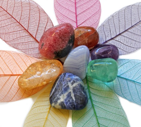 Close up of Chakra Crystals on coloured skeleton leaves