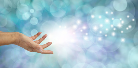 Magical Moment  -  Female hand appearing to throw out white glittering sparkles across a beautiful blue bokeh background with plenty of copy space