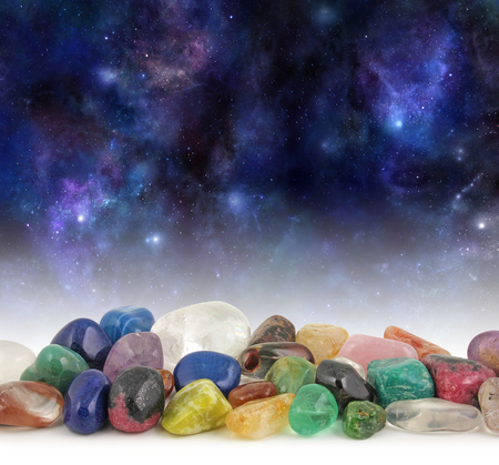 Cosmic Healing Crystals - Deep space background with stars, suns and planets with a selection of multicolored tumbled healing crystals at the front and plenty of copy space above