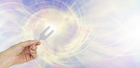 Photo for If you could see the sound waves make by an Angel Tuning Fork - female hand holding a short aluminum tuning fork on a graphic depiction of angelic sound waves background - Royalty Free Image