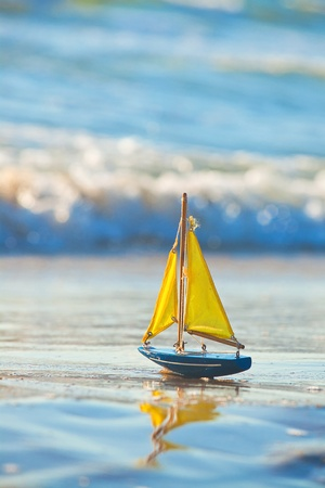 Foto per The little toy boat stands on sandy beach - Immagine Royalty Free