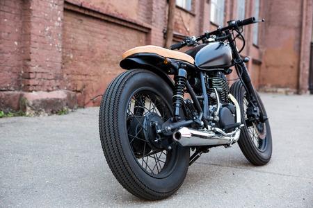 Foto de Black vintage custom motorbike motorcycle caferacer in front of brick wall. Back view. - Imagen libre de derechos