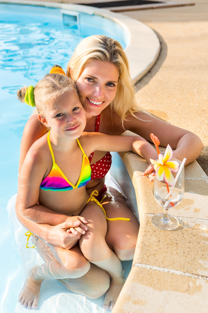 Outdoor portrait of beautiful blonde mother mother in bikini and her cute daughter in swimsuit. Little girl and her mammy look to the camera and smile. Happy family at the pool. Happy Mothers day.