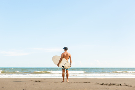 Handsome fit man stand with white blank surfboard wait for wave on surf spot at sea ocean beach. View from back. Concept of sport, fitness, freedom, happiness, new modern life, generation Y.