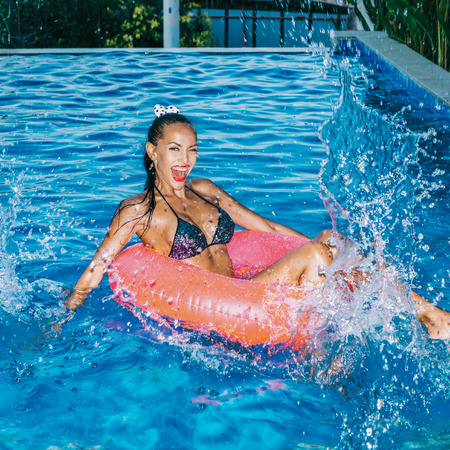 Photo for Sensual tanned woman with long legs swims in big pink inflatable circle in swimming pool. She plays and sprinkling water - Royalty Free Image