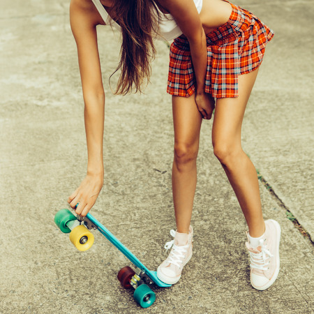 Foto de Skinny young lady in a sexy red tartan mini skirt and sunglasses hold her blue penny skateboard shortboard while stands on the tropical street. Outdoor lifestyle picture on a sunny summer day. - Imagen libre de derechos