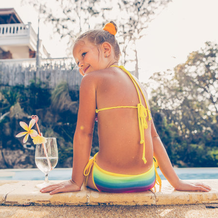 Photo pour Cute little blonde girl swimming in big pool. Big glass with water, straw and frangipani stay on the pool edge. Little lady sit on the edge of the pool. Sunbathing and leisure on sunny summer day. - image libre de droit
