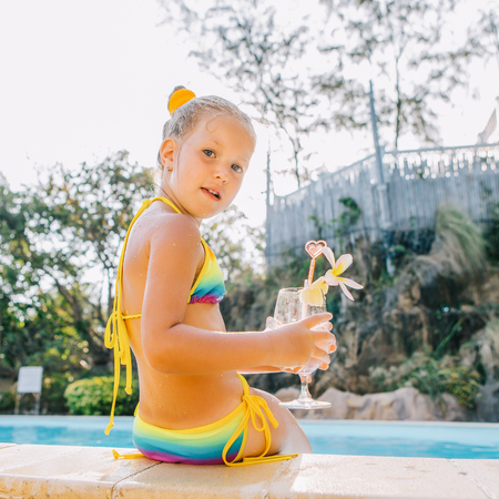 Photo pour Cute little blonde girl swimming in big pool. She sit on the pool edge. Little lady hold big glass with water, straw and frangipani and look to the camera. Sunbathing and leisure on sunny summer day. - image libre de droit