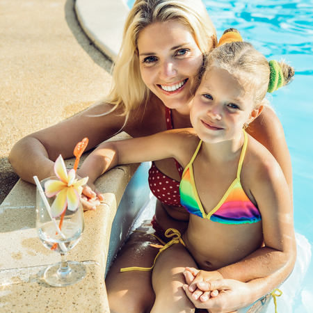 Foto de Outdoor portrait of beautiful blonde woman mother in bikini and her cute daughter in swimsuit. Little girl and her mammy look to the camera and smile. Happy family at the pool. Happy Mothers day. - Imagen libre de derechos
