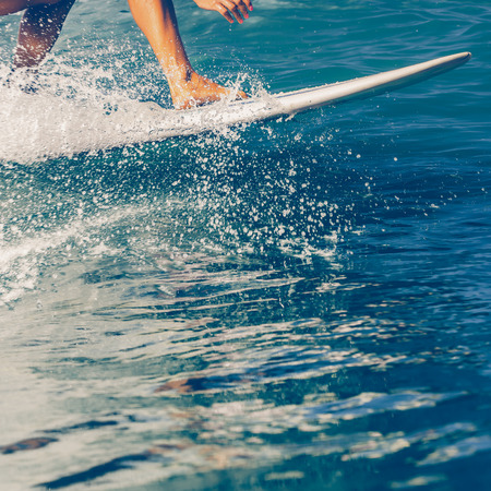 Foto per Close up of beautiful young Sporty girl in a bikini swimsuit ride big wave with lot of splashes. Sporty surfer woman surfing in Mauritius in the Indian Ocean on the transparent waves. Active Lifestyle - Immagine Royalty Free