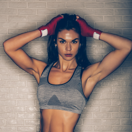 Photo for Young beautiful female pose after workout functional crossfit training. Strong muscular sporty girl ready for active exercise in sport gym. Strength and motivation concept. Self defense training. - Royalty Free Image