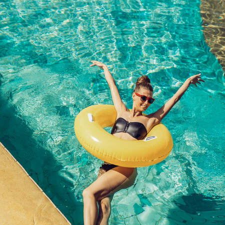 Photo pour Happy beautiful woman in trendy swimsuit and sunglasses have fun in hotel swimming pool party. Young sexy girl enjoying holiday, having fun and sunbathing on inflatable yellow ring in cool water. - image libre de droit