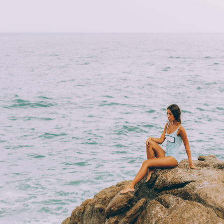 Photo pour Pretty girl in full body swimsuit with long healthy hairs sit on big stone on the rock beach during sea ocean storm and touch her knee. Big waves near her legs. Concept of danger, sad, bad emotions. - image libre de droit