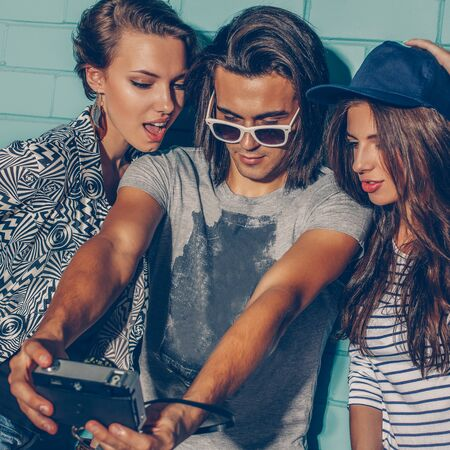 Photo pour Lifestyle portrait of beautiful best friend hipsters wearing stylish bright outfits and having great time. Handsome boy with two beautiful girls taking selfie self portrait photo with film camera in front of blue brick. - image libre de droit