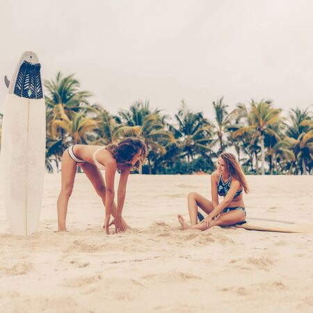 Photo pour Two surfing girl with shortboard surfboard surf board in sexy bikini on a beach stretching before go to the big ocean waves on sunrise or sunset. Modern active sport lifestyle and summer vacation. - image libre de droit