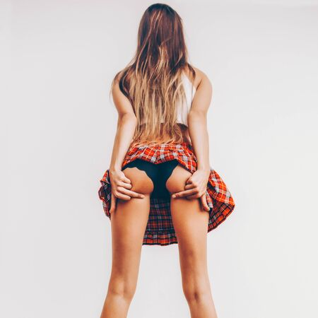 Photo pour Skinny lady in a sexy red tartan skirt with fit ass show middle finger, fuck you off sign in front of a white wall. Outdoor funny lifestyle portrait, concept of brutal, rebel, punk, furious, indecent - image libre de droit