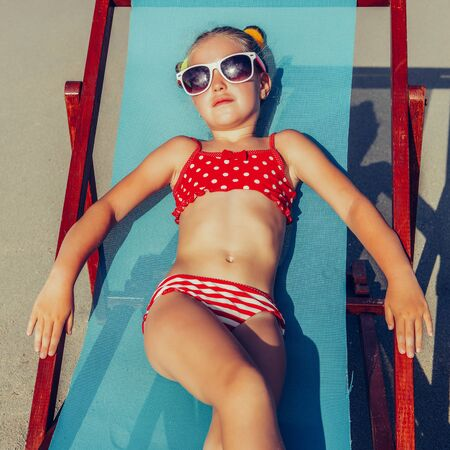 Photo for Cute little girl in red swimsuit and sunglasses enjoying on a sun lounger rest on the beach chair on tropical sandy beach sea shore. Sunbathing and leisure on sunny day. - Royalty Free Image