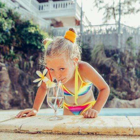 Foto de Cute little blonde girl swimming in big pool. Big glass with water, straw and frangipani stay on the pool edge. Little lady smile and drink from the glass. Sunbathing and leisure on sunny summer day. - Imagen libre de derechos