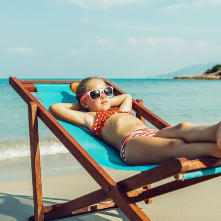 Foto de Cute little child in red swimsuit and white sunglasses enjoying on a sun lounger rest on the beach chair on tropical sandy beach sea shore. Sunbathing and leisure on sunny day. - Imagen libre de derechos