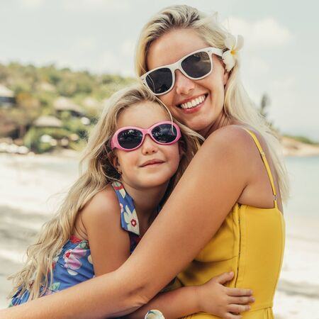 Photo pour Outdoor portrait of beautiful blonde mother and her cute daughter. Small girl and her mammy look to the camera on the beach. Little lady and mom wearing sunglasses. Summer sunny day Happy Mothers day. - image libre de droit