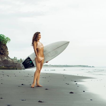 Foto per Surf girl with long hair go to surfing. Slim surfer woman holding surfboard on a beach and ready to have fun in ocean water. Bali island, Indonesia. Outdoor Active Lifestyle. It's time for surfing! - Immagine Royalty Free