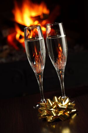 glasses with champagne with golden bow, fire as the background