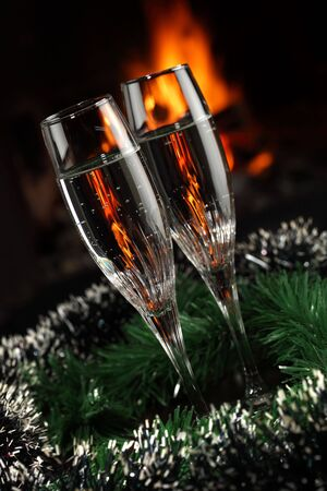 glasses with champagne with christmas entourage, fire as the background