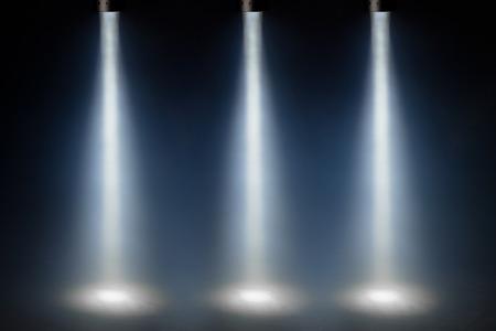 three blue spot lights on stage