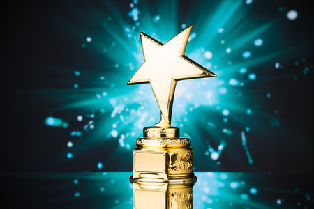 gold star trophy against blue sparks background