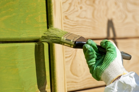 hand with a paint brush painting wooden wall in green outdoor shot