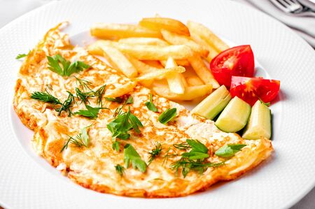 Photo pour egg omelet with fried potatoes, fresh vegetables, green dill and parsley close-up on white plate - image libre de droit