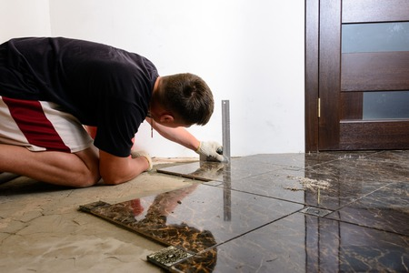 A person with a laser level checks the installed floor tile