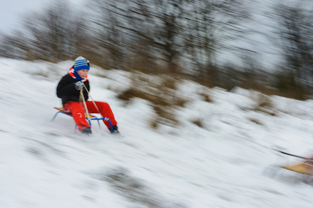 Photo for the boy descends from the hills in the sled, the movement is blurred 2019 - Royalty Free Image