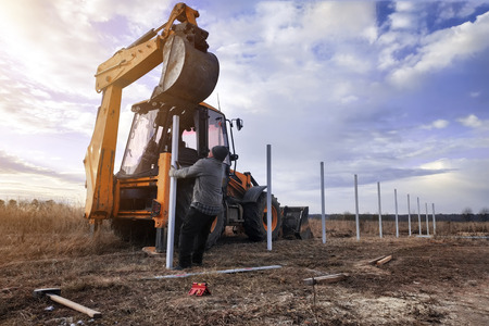 Photo for The excavator clogs profile pipes on the fence 2019 - Royalty Free Image