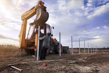 Photo pour The excavator clogs profile pipes on the fence 2019 - image libre de droit