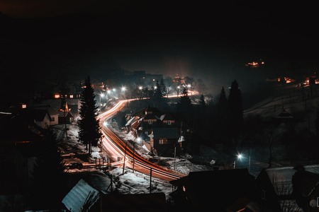 Magnificent night landscape of the Ukrainian village in bright light and blurred automobile lights